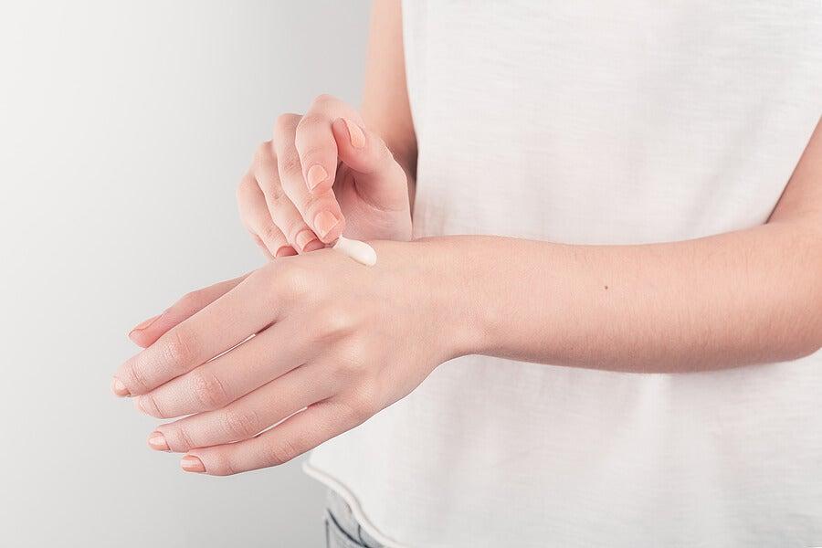 Persona aplicándose crema Diprogenta en la mano.