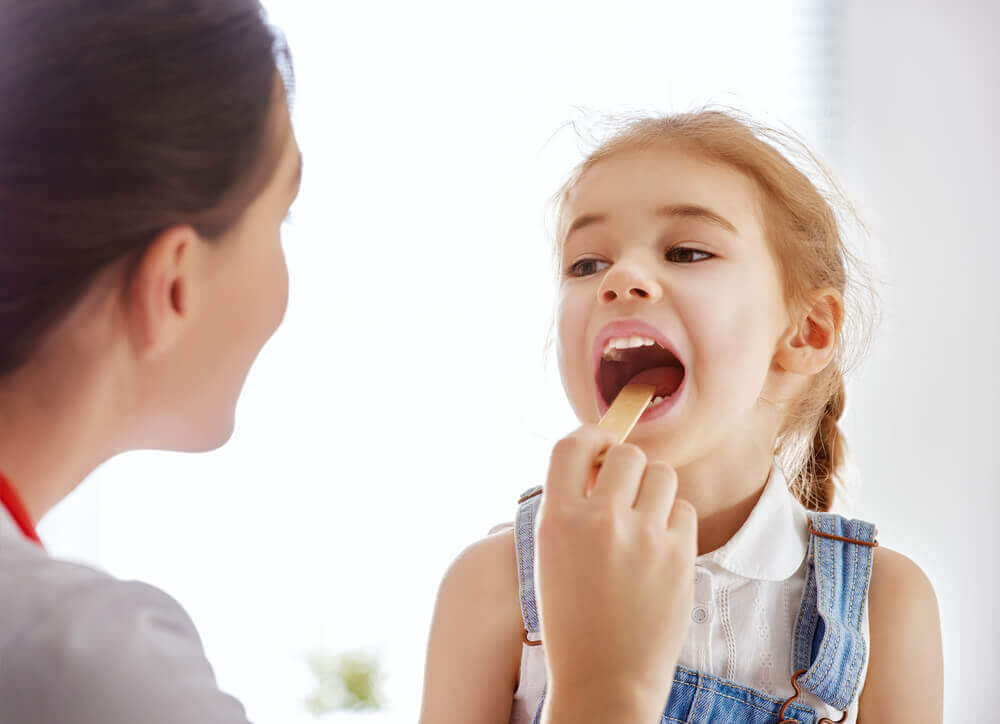 Niña con placas en la garganta