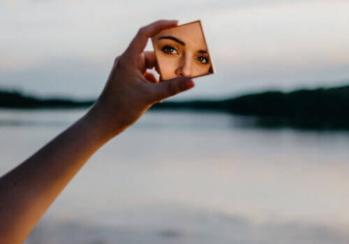 Mujer mirándose en un espejo pensando en recuperar la autoestima después de una ruptura