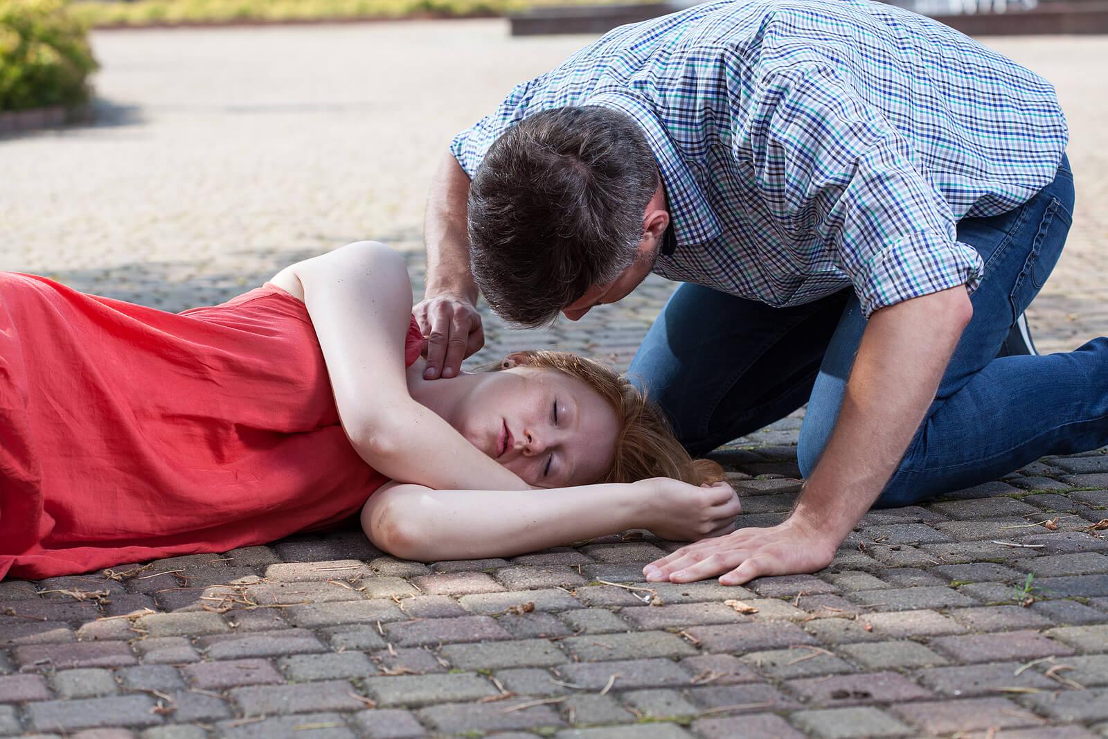 Hombre comprobando pulso de la chica desmayada en la calle.