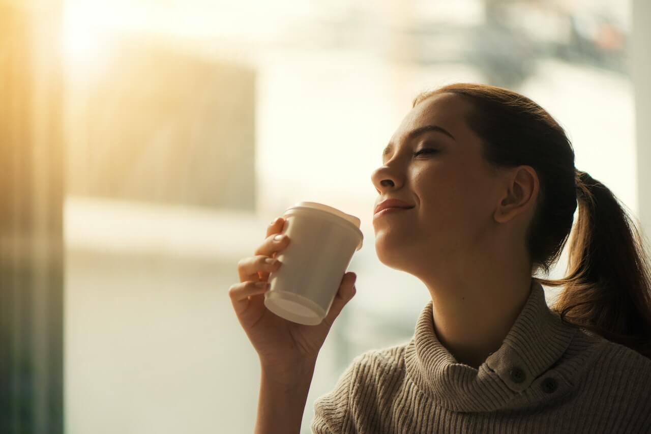 Mujer apreciando el aroma del café.