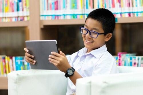 niño con miopía mira una tableta