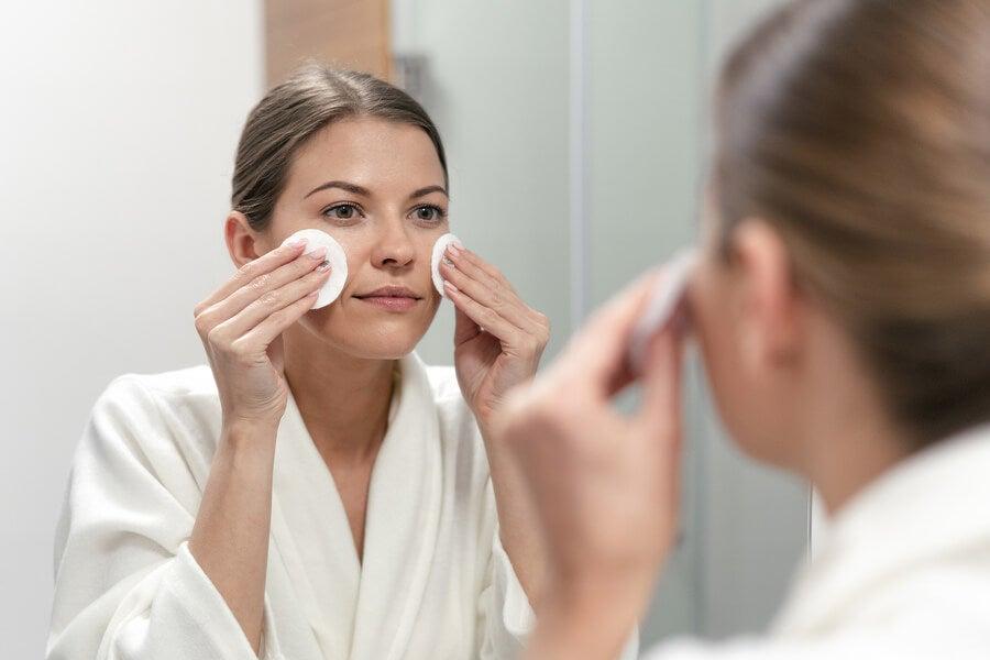 Mujer limpiando su piel con pomos