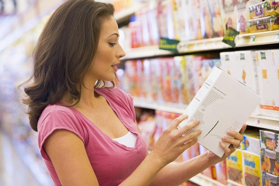 Mujer lee etiquetas de botanas saludables.