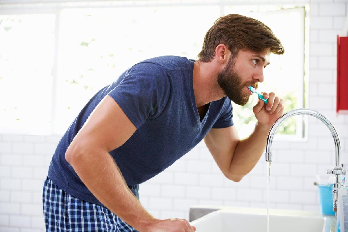 Hombre cepilla sus dientes.