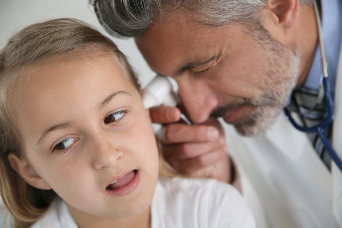 Médico examina oído de niña.