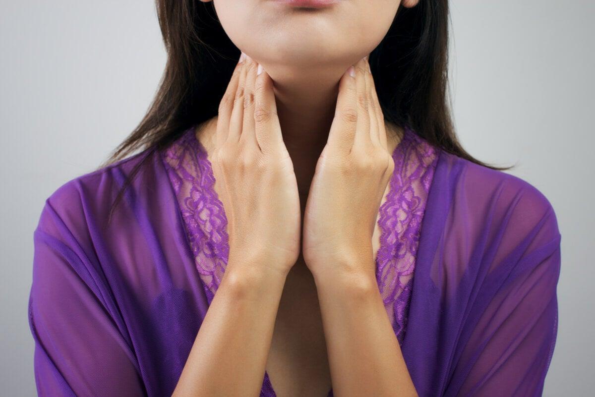 Mujer toca su tiroides en el cuello