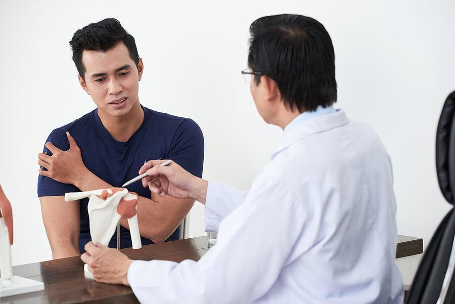 Doctor viendo a un paciente con calcificación en el hombro