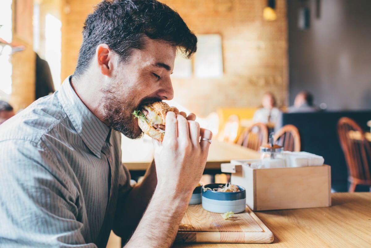 Hombre come rápido una hamburguesa.