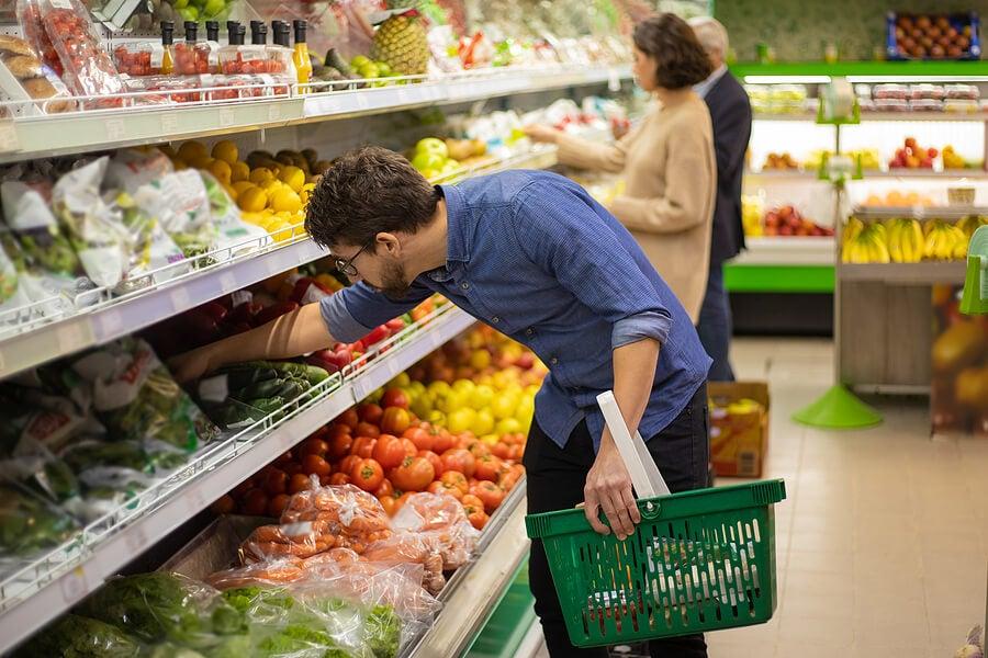 Hombre eligiendo verdura en el supermercado.