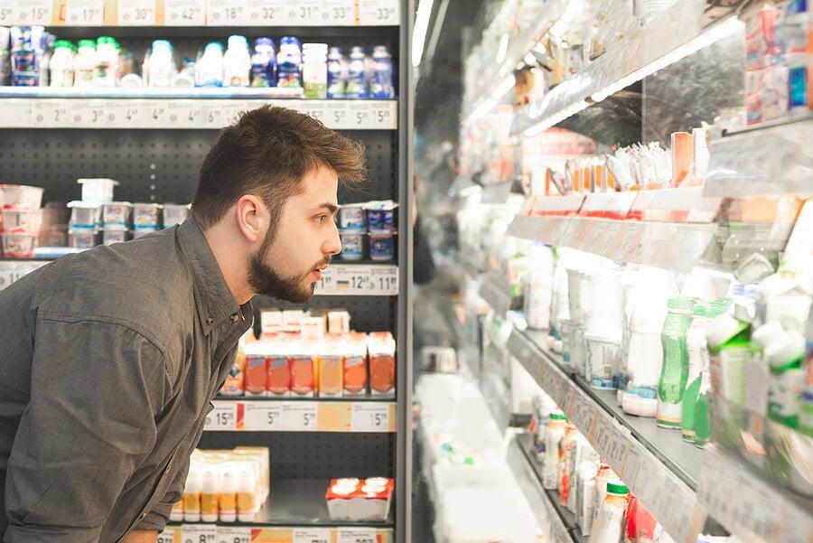 Hombre mirando productos lácteos en el supermercado.