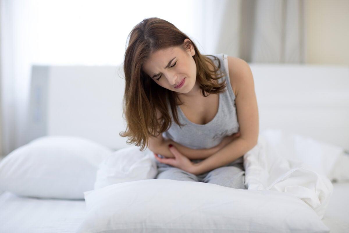 Mujer con dolor abdominal en la cama.