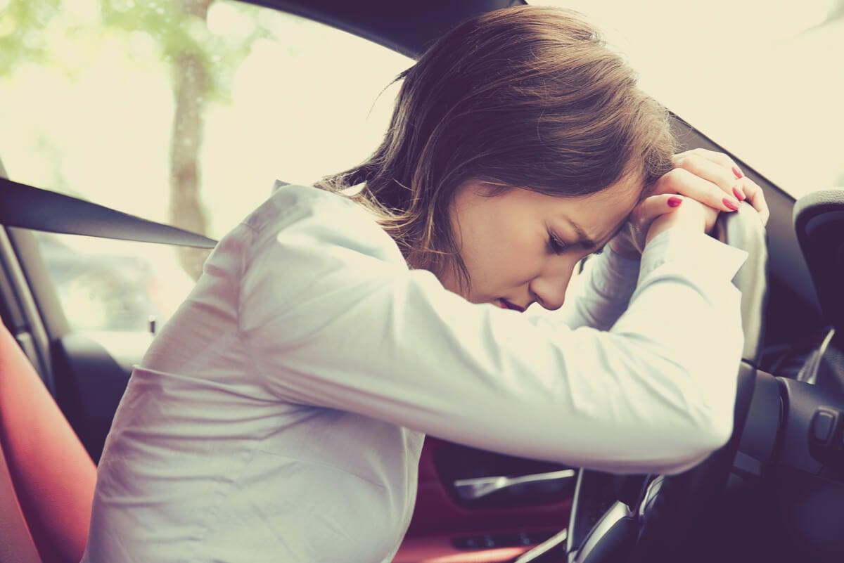 Mujer estresada en el vehículo.