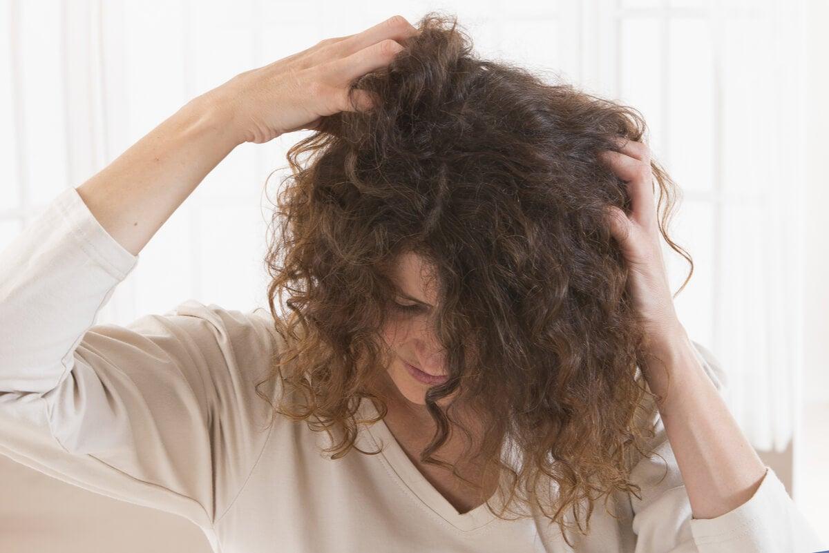 Mujer se rasca el cuero cabelludo.