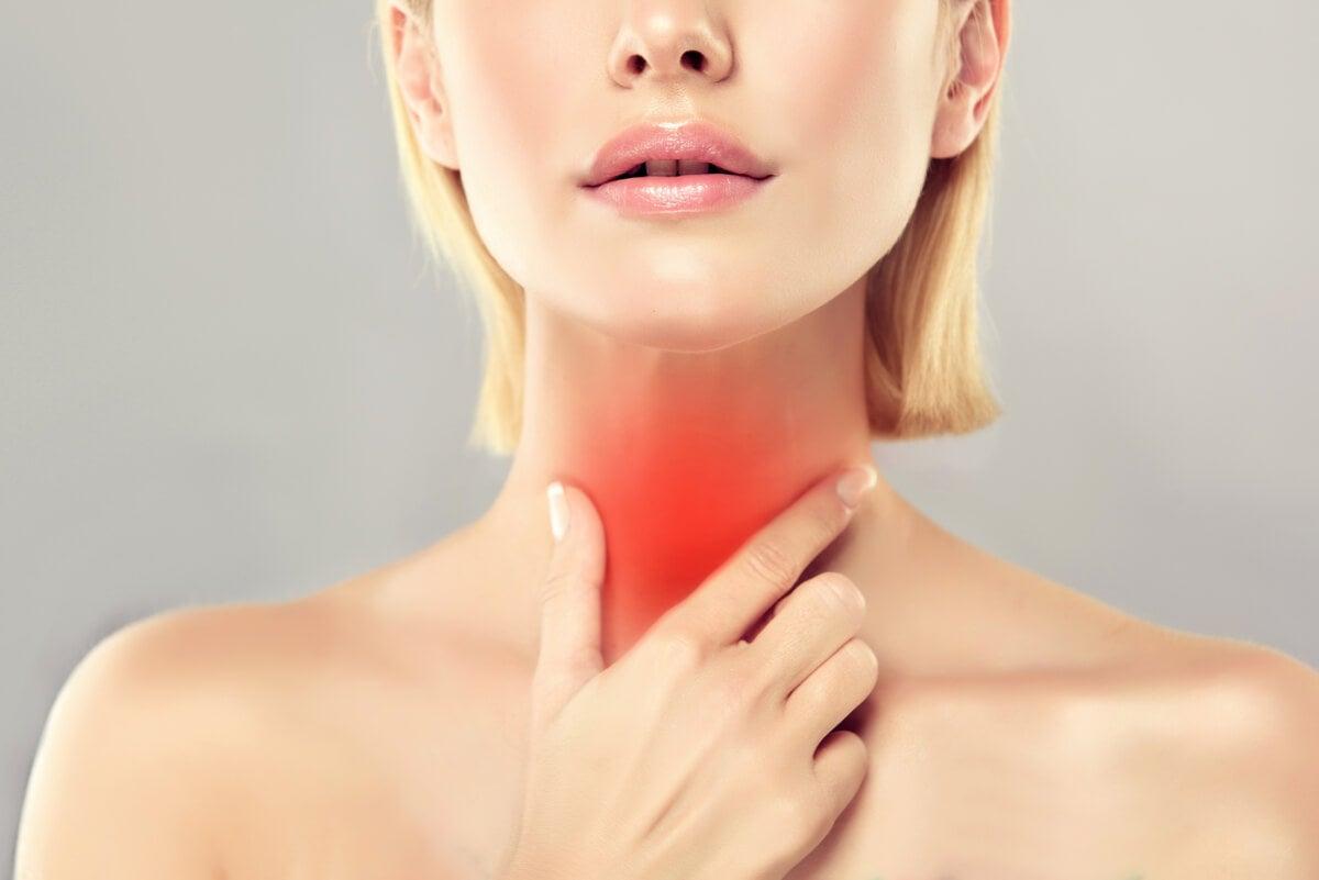 Mujer tocando su glándula tiroides.