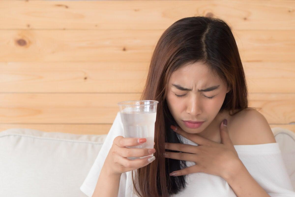Mujer toma agua porque padece hipo.