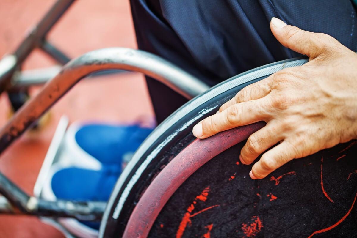 Persona en silla de ruedas por poliomielitis.