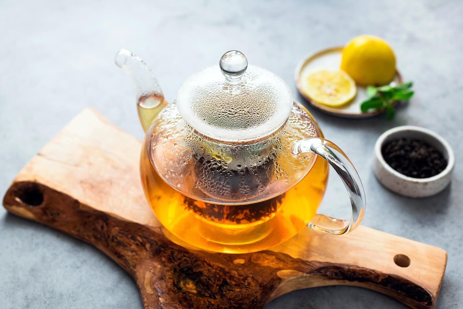 Jarra de té de verde con limón y clavos.