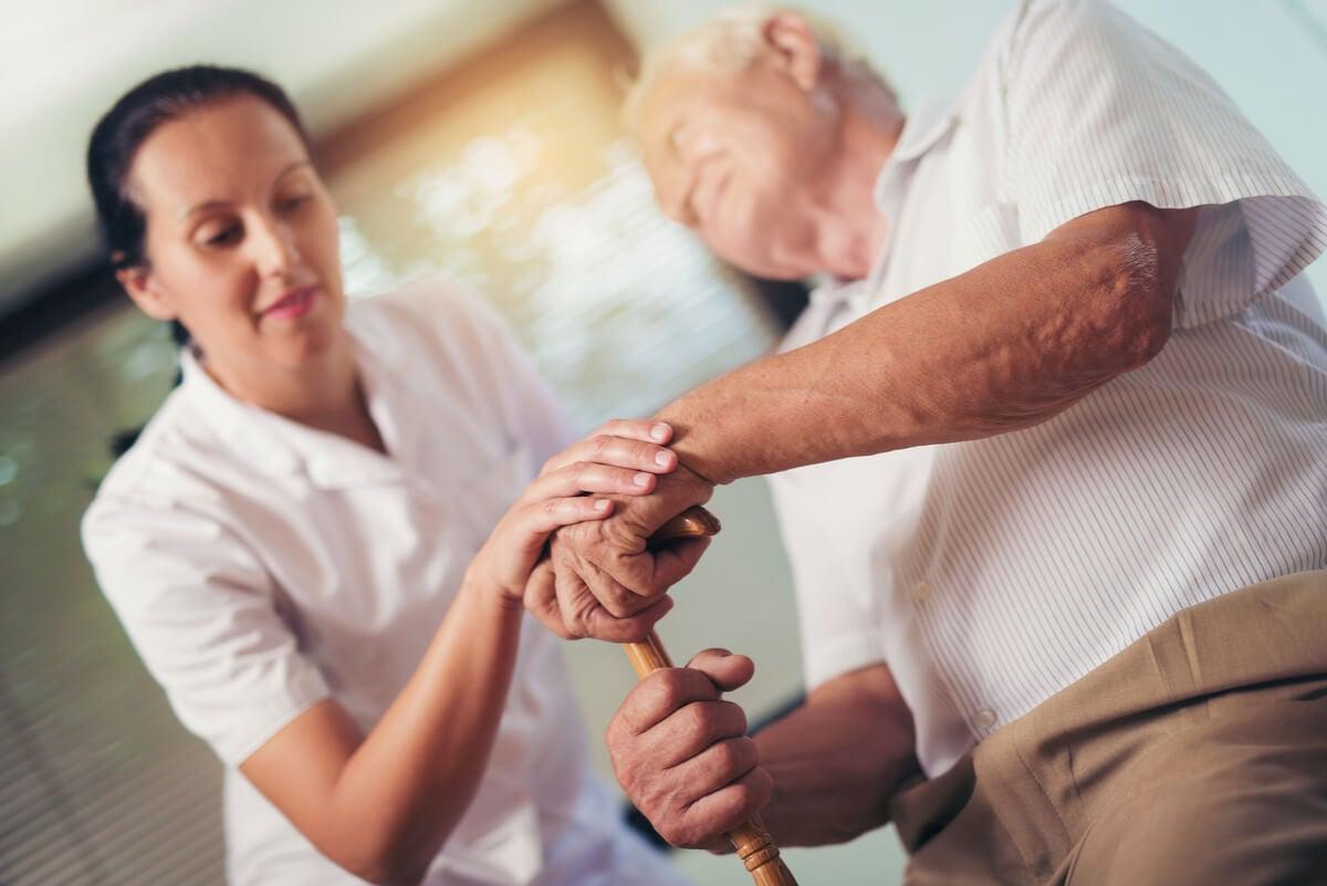 Anciano ayudado por cuidador.