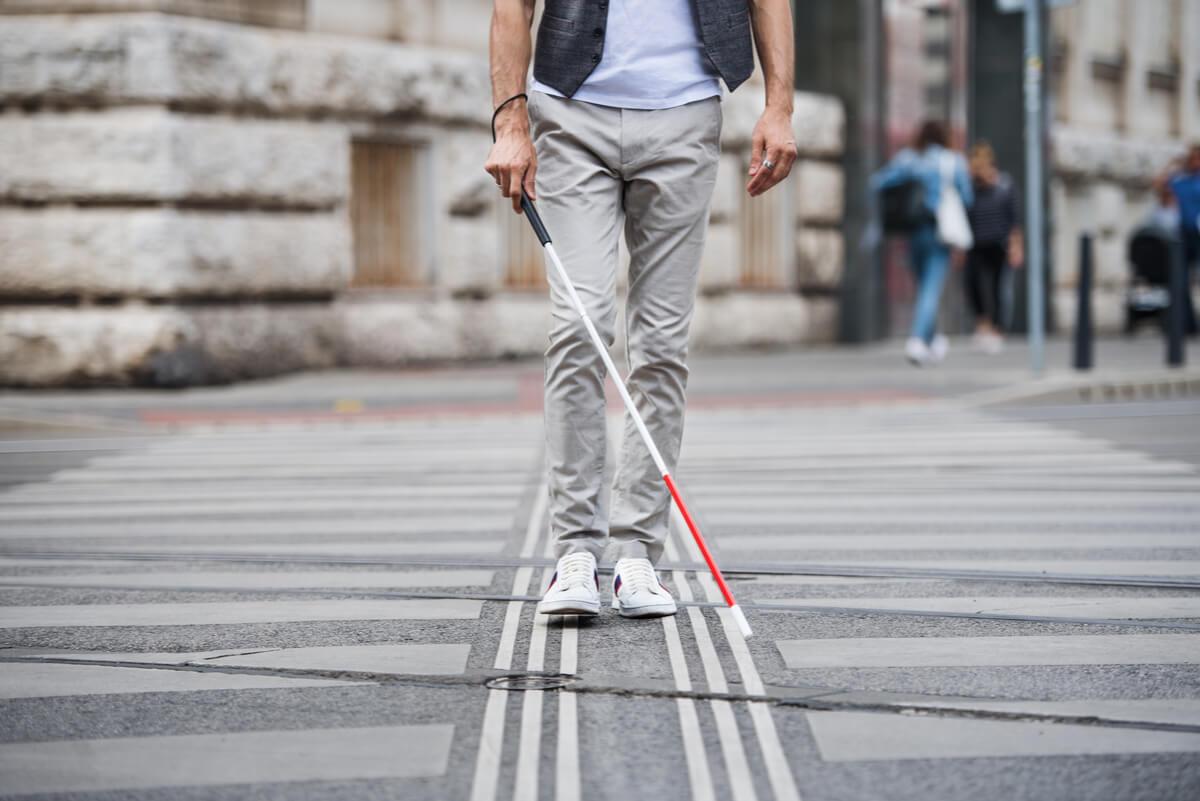 Hombre ciego con bastón blanco.