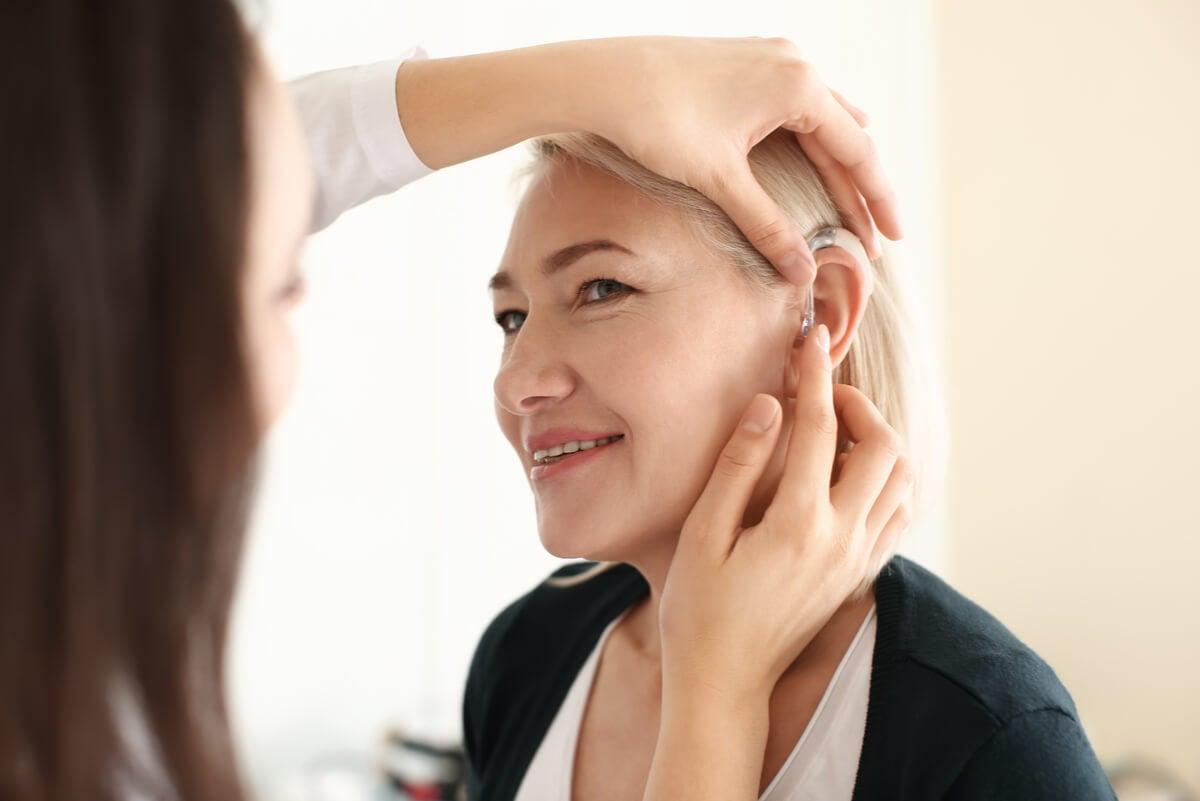 Audífono en una mujer por pérdida de audición por envejecimiento.