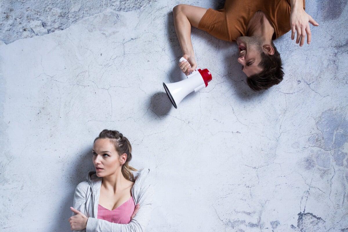Hombre grita a mujer con megáfono.