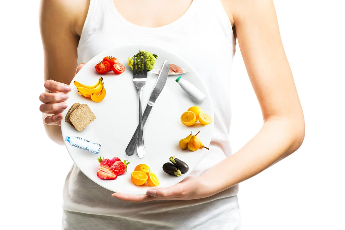 Mujer sostiene reloj de alimentos.
