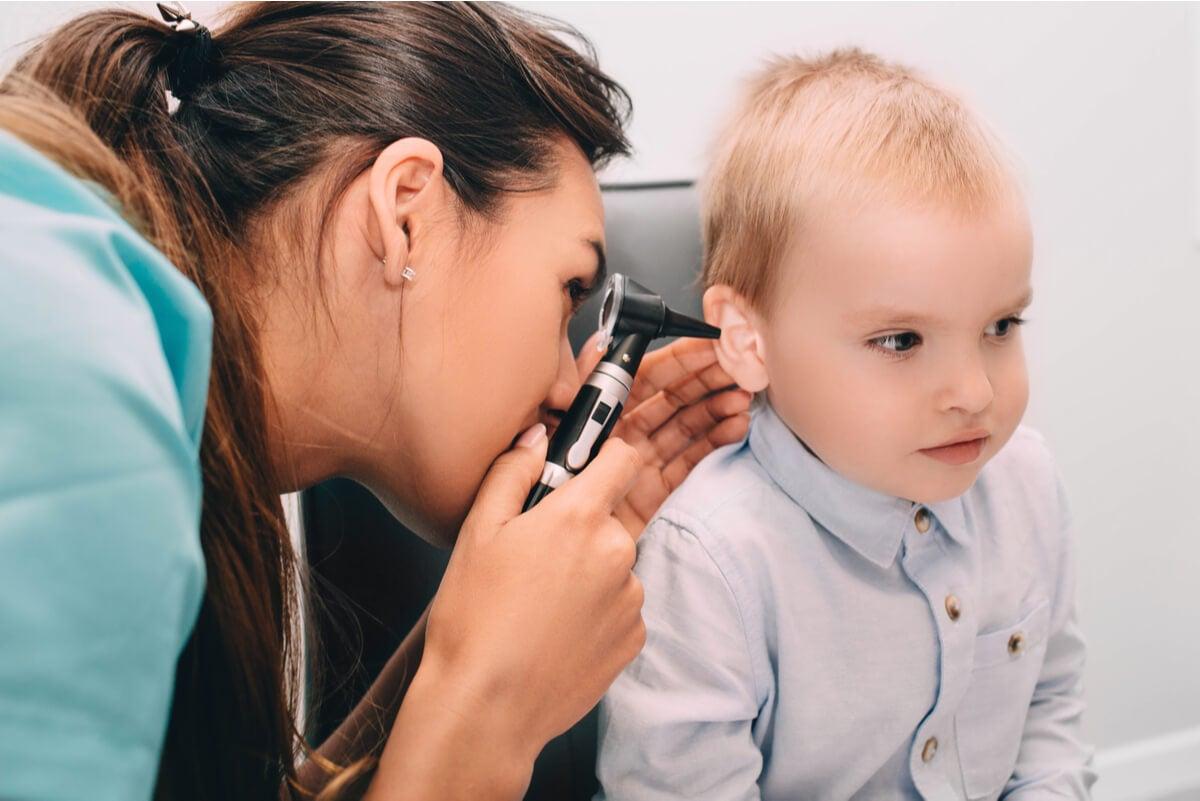 Pediatra revisa oído de un niño.