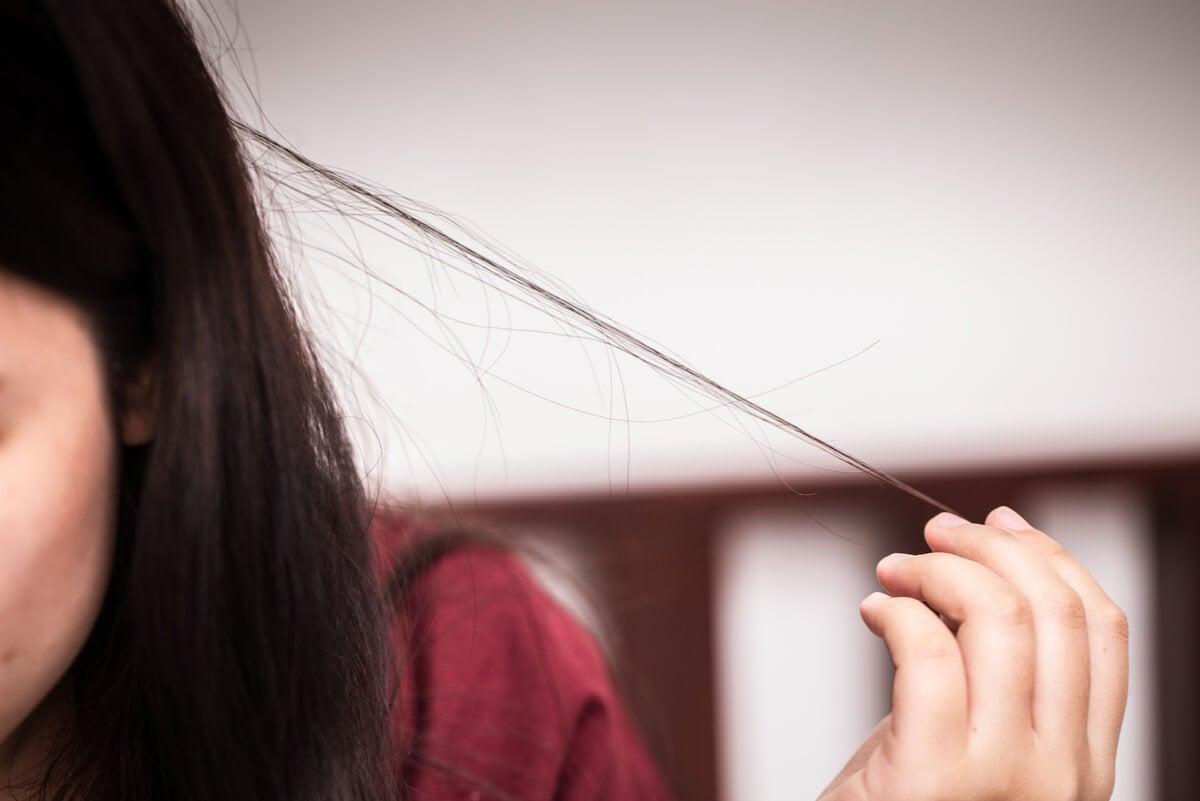 Mujer estira su cabello para luego comerlo.