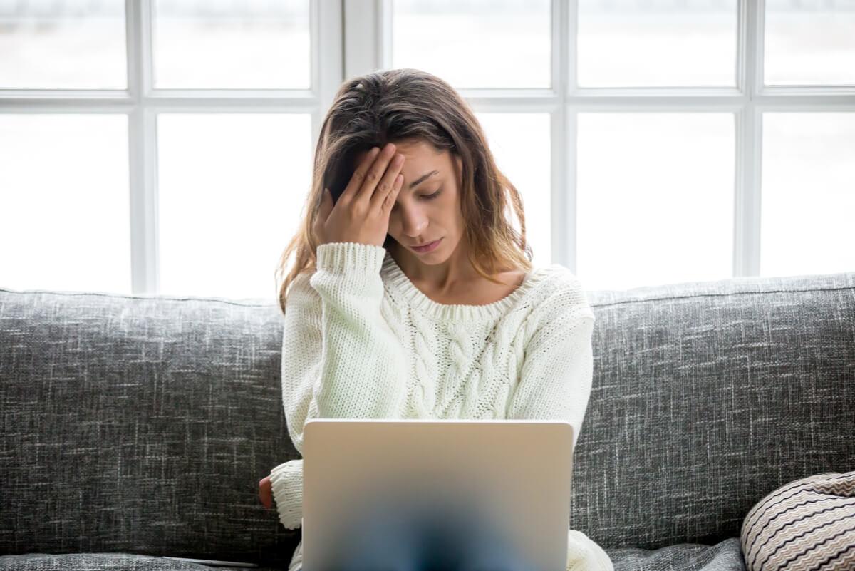 Mujer estresada frente a computadora.