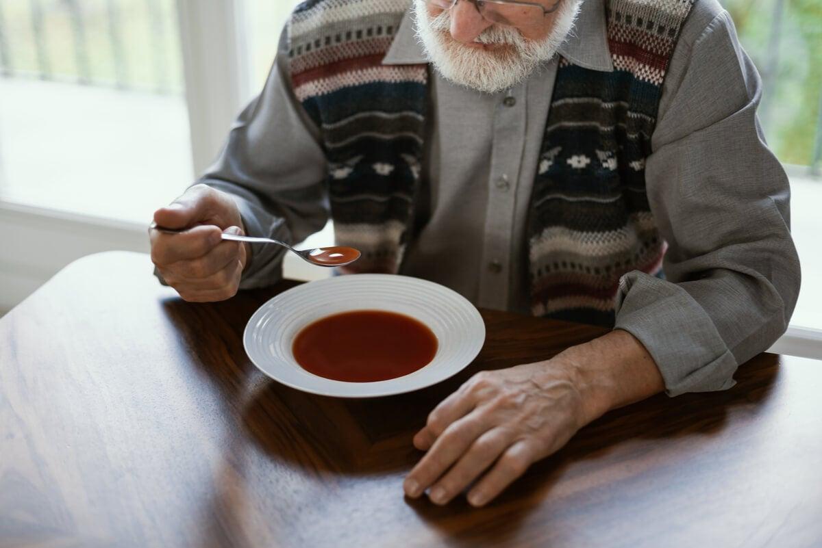 Anciano con párkinson cenando.