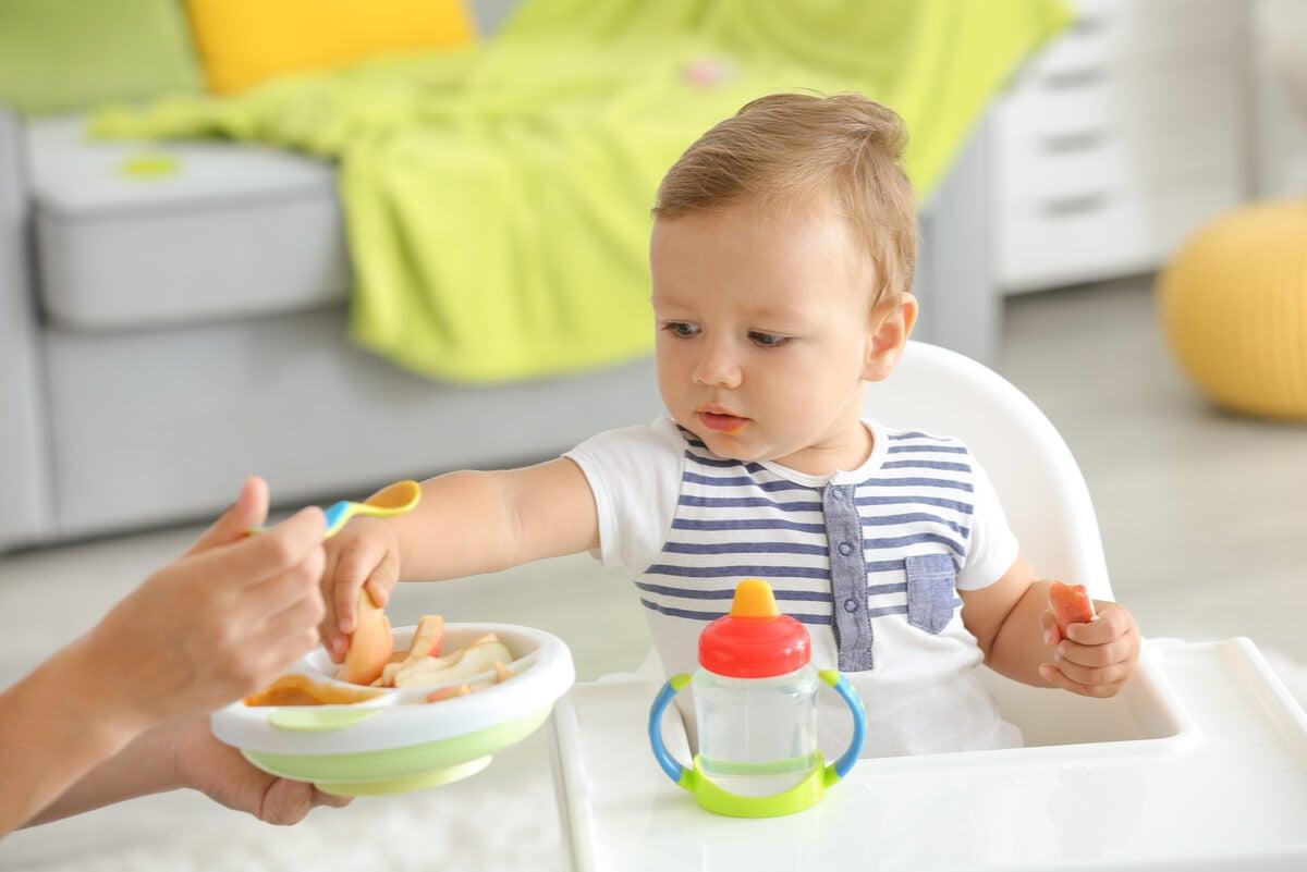 Bebé toma alimentos con la mano.