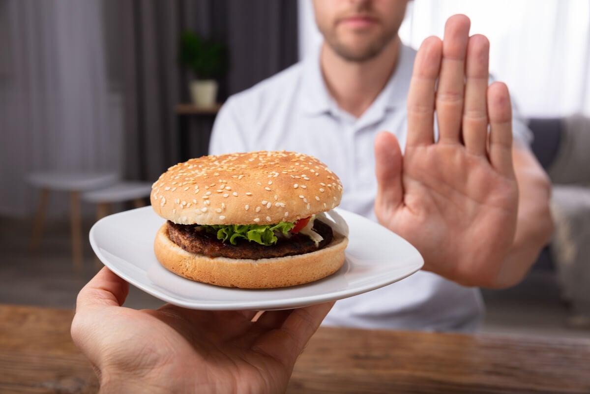 Hombre rechaza comida que causa acidez.