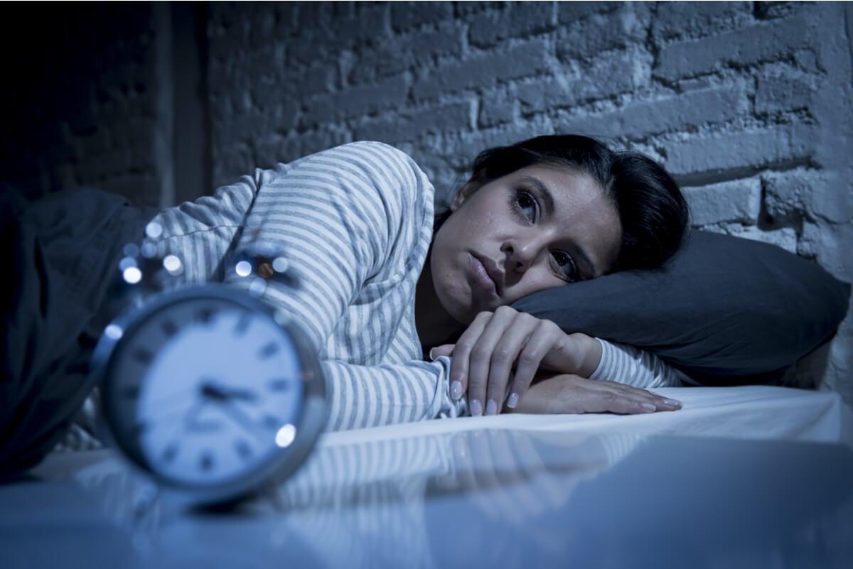 Mujer con insomnio y reloj.
