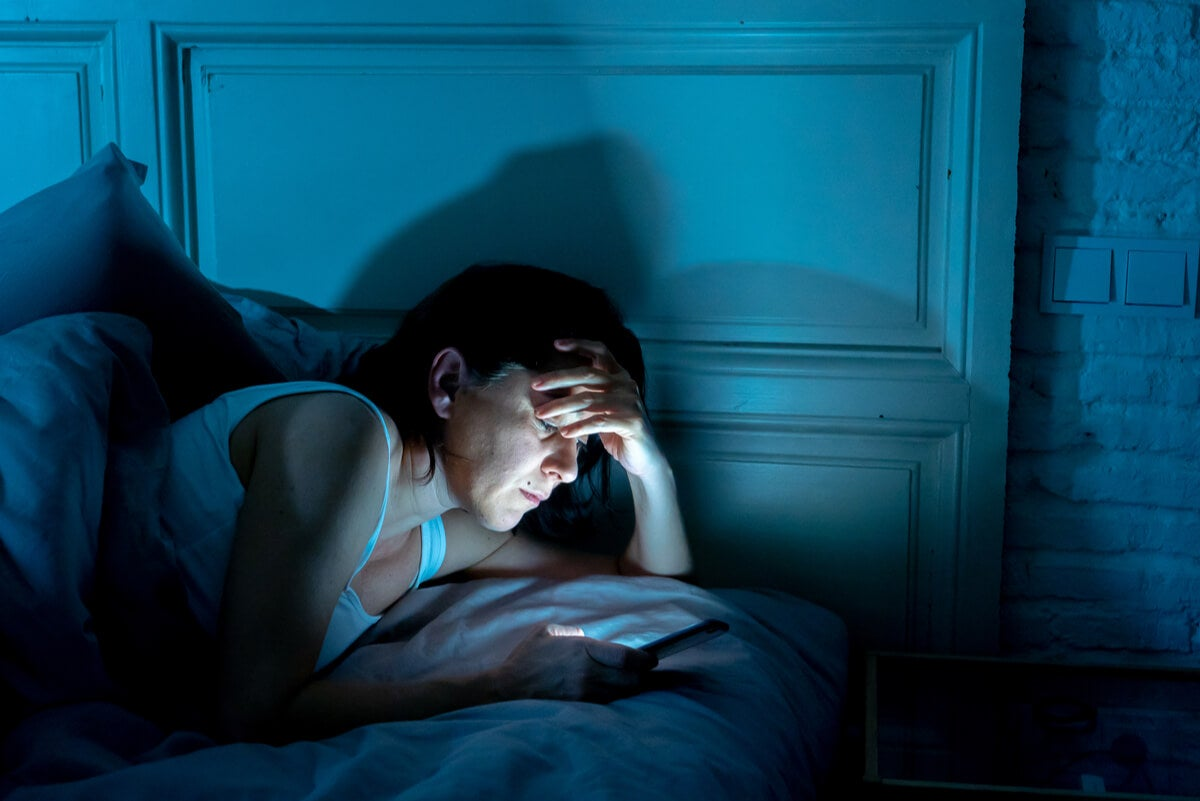 Mujer lee celular durante la noche en la cama.
