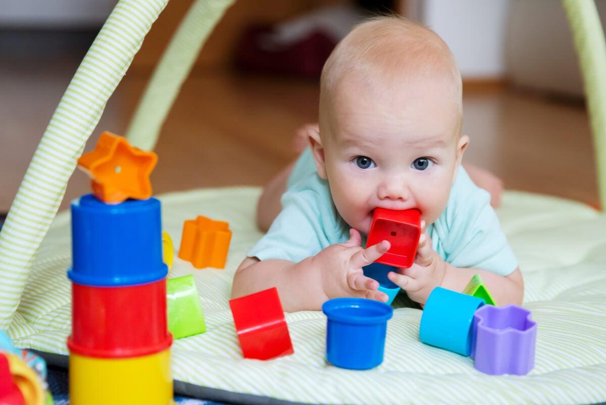 Bebé juega con cubos y mira algo fijamente.
