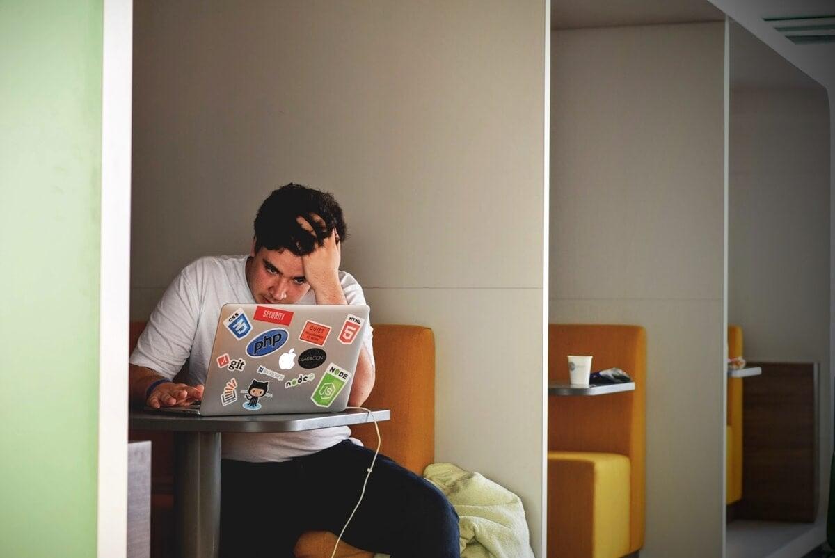 Chico con ordenador representando la depresión en estudiantes universitario.