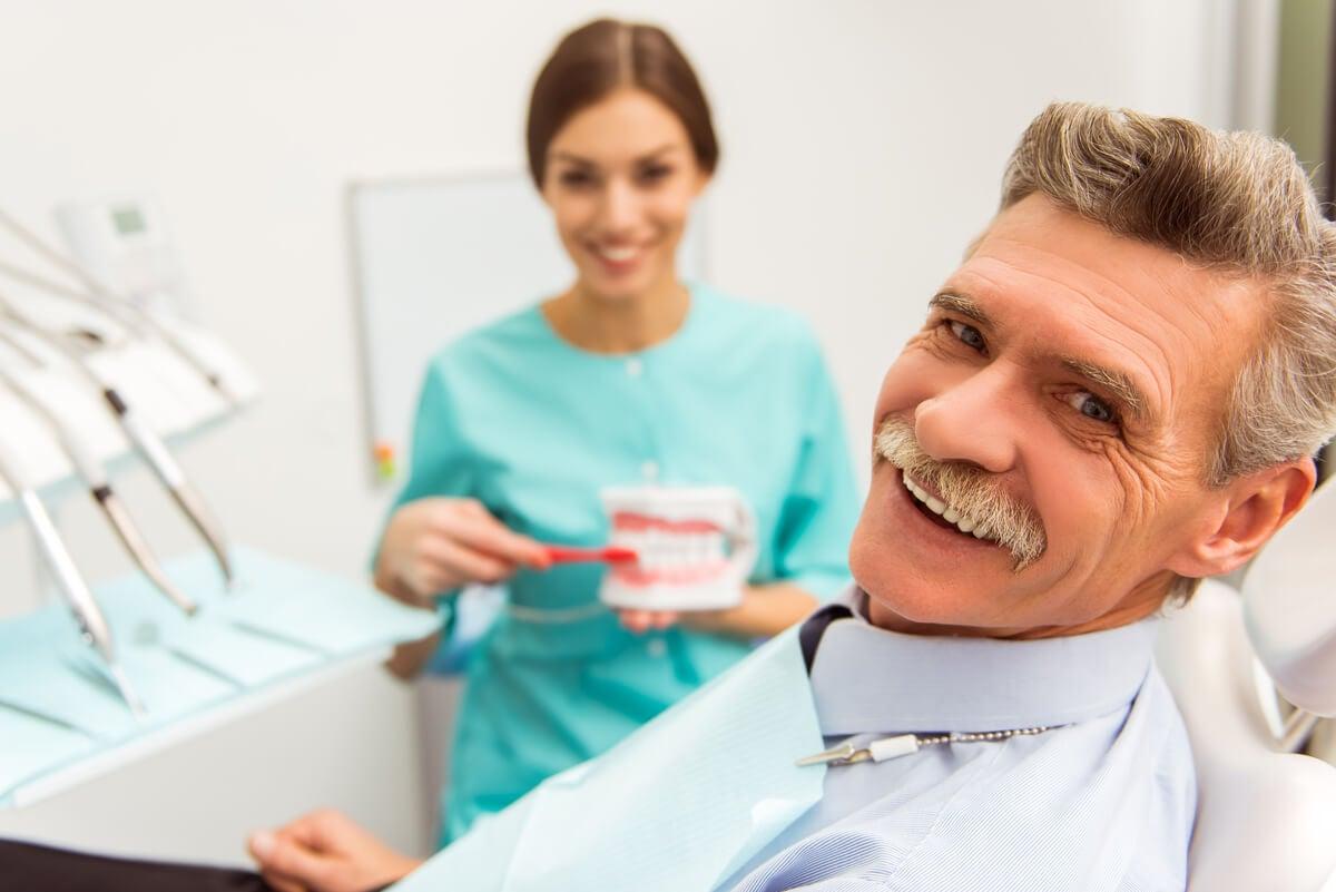 Hombre mayor en consulta con dentista por complicaciones de los implantes dentales.