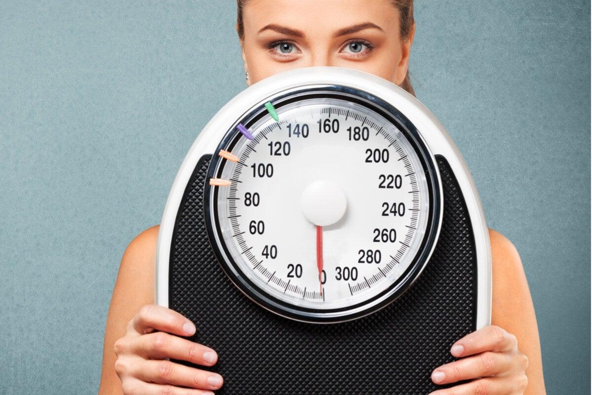 Mujer con balanza midiendo la dieta Sirtfood.