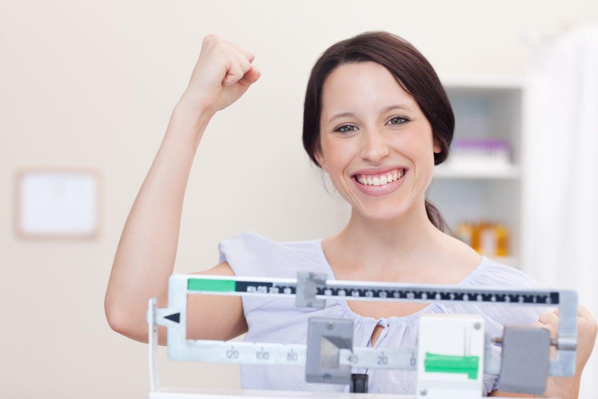 Mujer festeja el éxito de una dieta para bajar de peso.