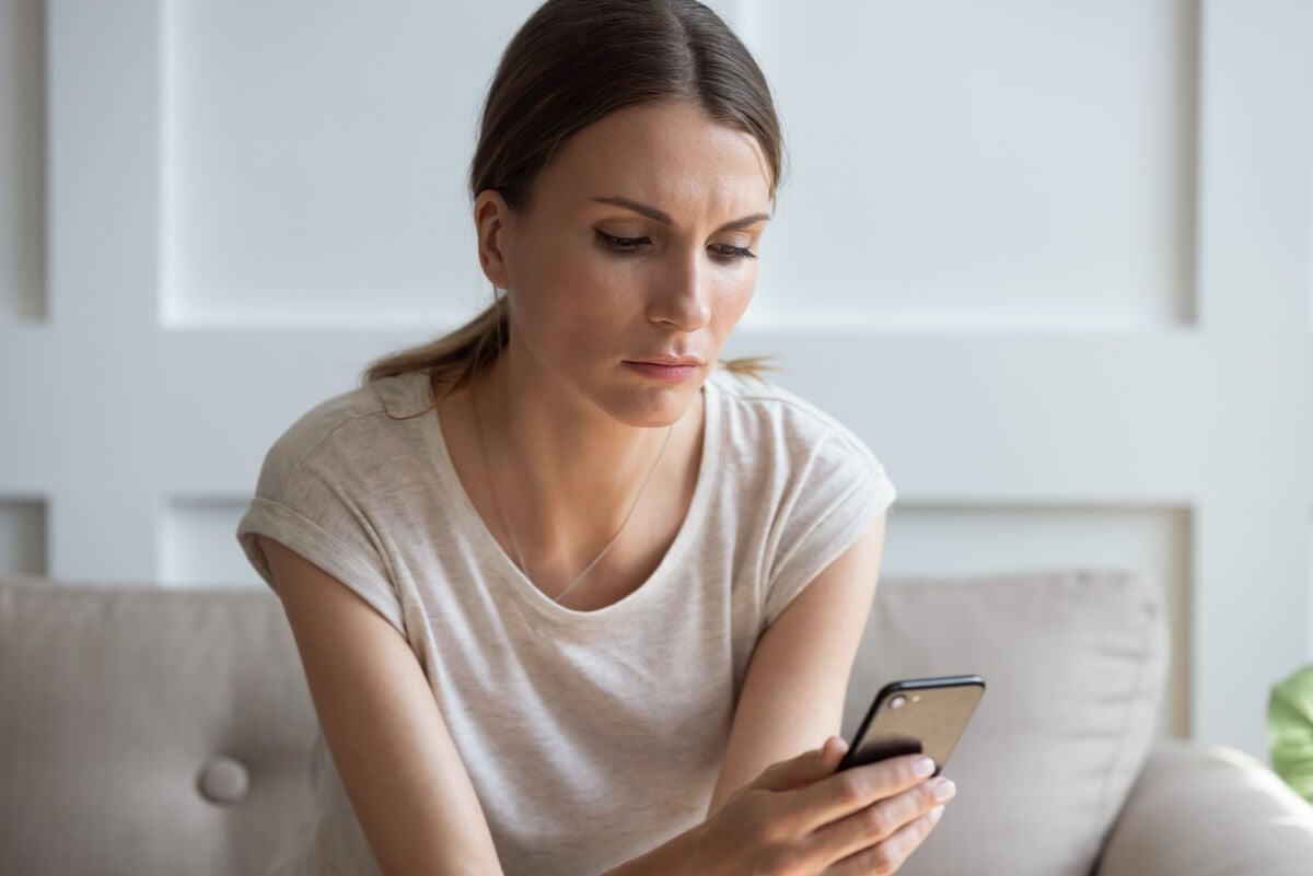 Mujer con estrés revisando el móvil.