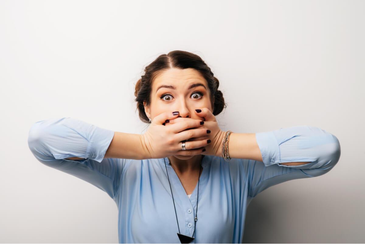 Mujer tapa su boca para no hablar.