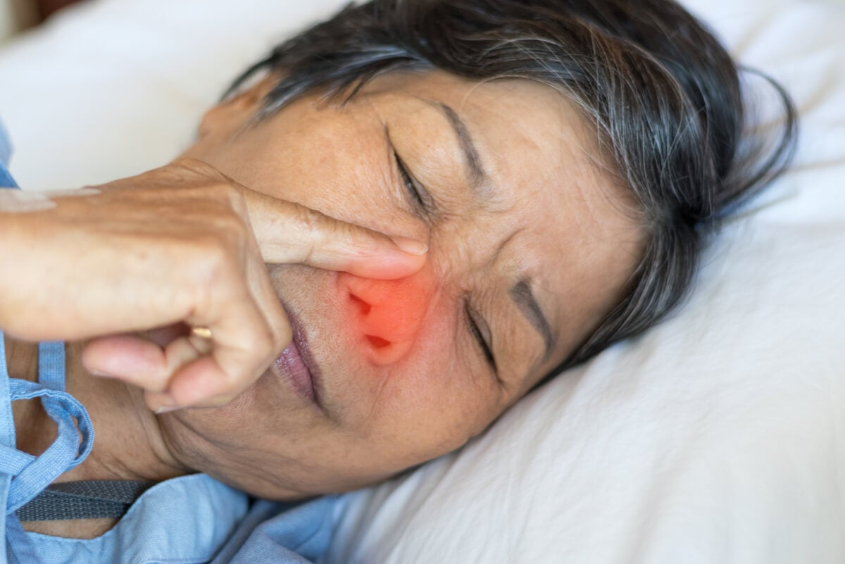 Mujer toca su nariz de dormida para comer mocos.