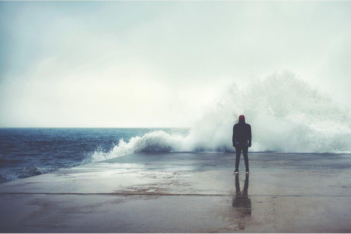 Persona frente al océano con miedo.