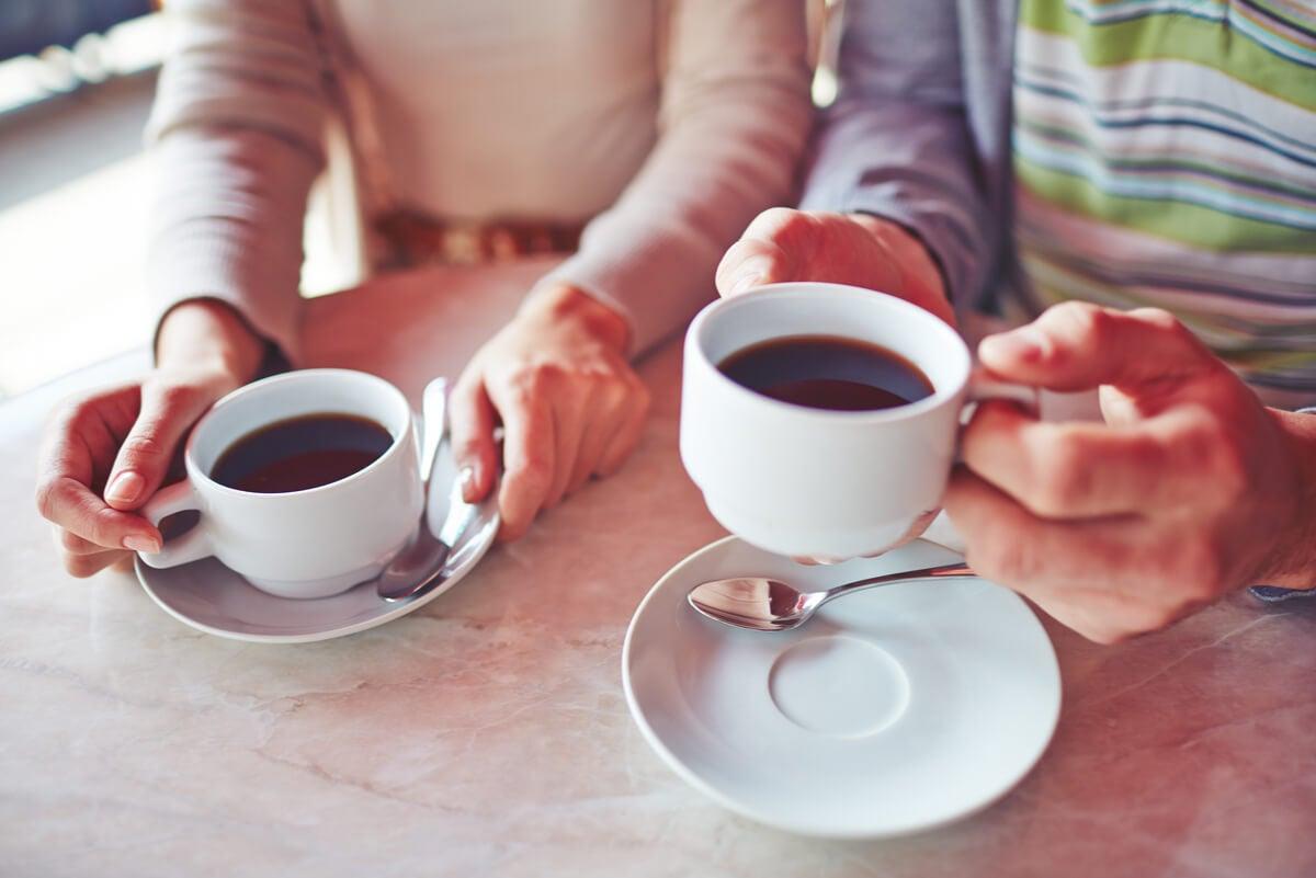 Tazas de café y manos.
