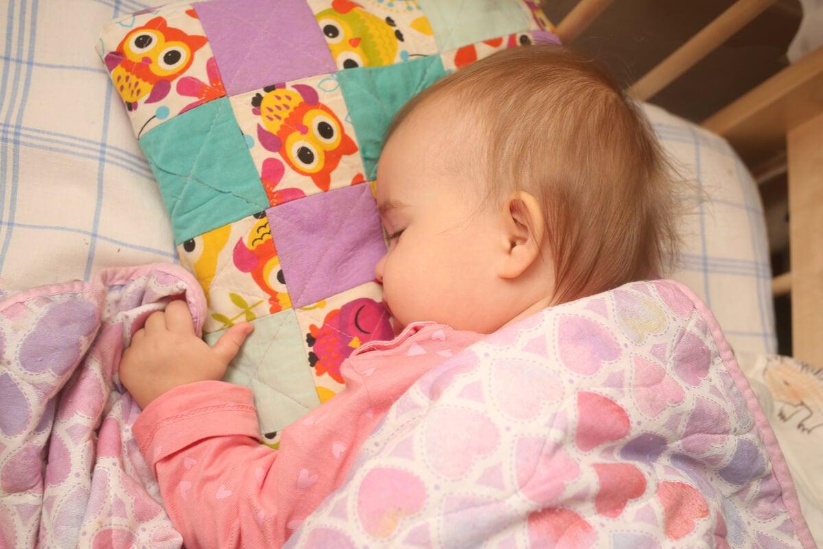 Bebé duerme con almohadones para no caerse.