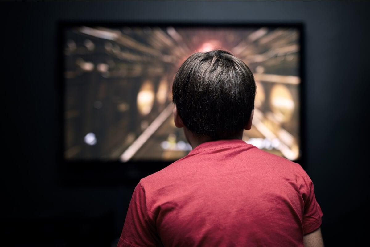 Joven mira televisor mediante Chromecast.