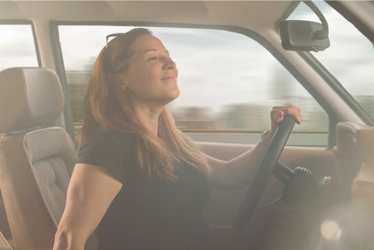 Mujer revisa los retrovisores con riesgo de accidente en su auto.