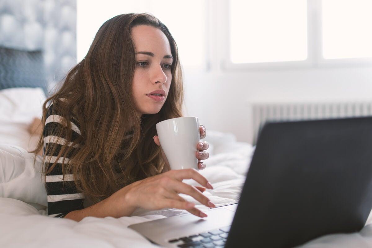 Mujer trabaja desde la casa en su cama con un ordenador.