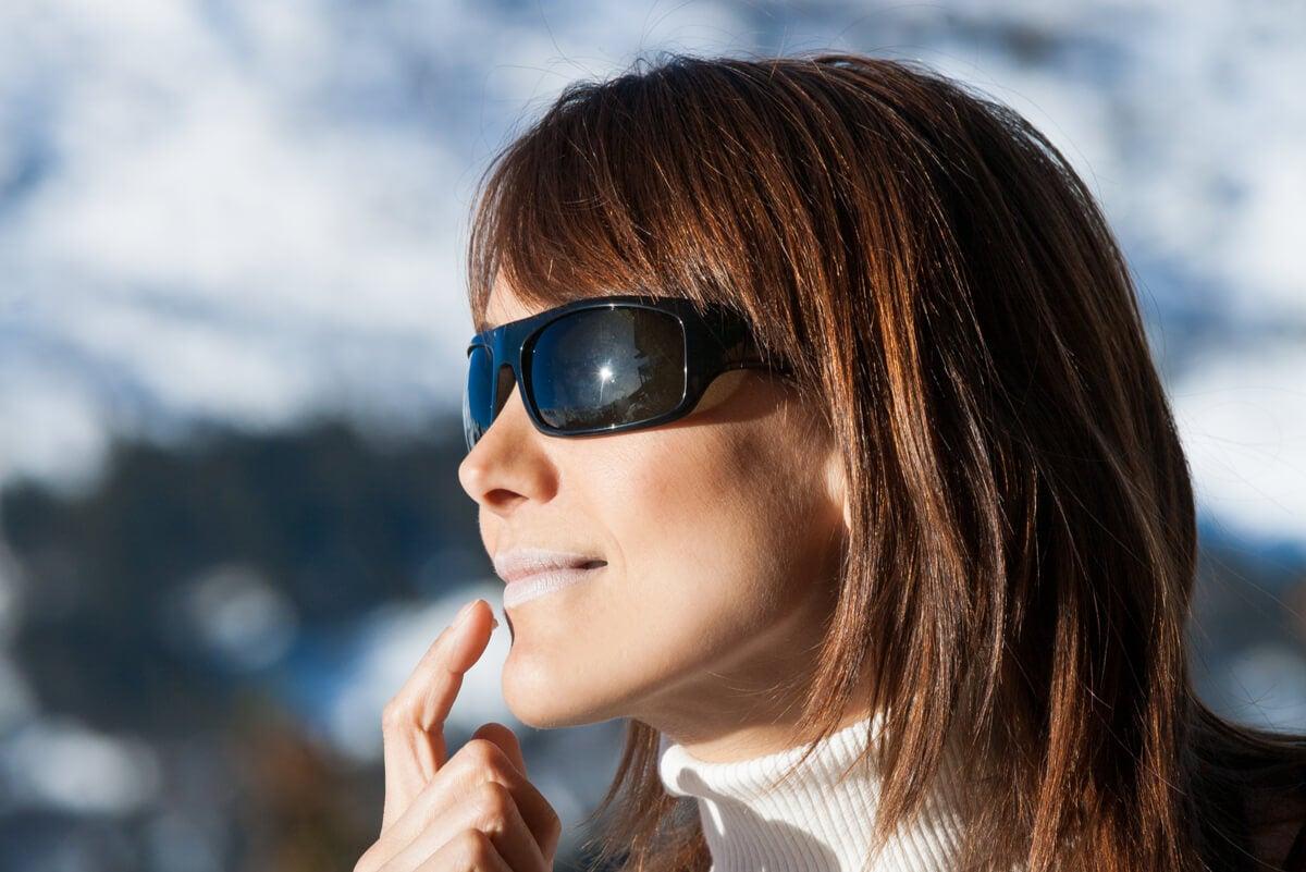 Mujer se coloca protector solar en los labios.